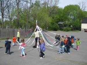 kids dancing around the maypole