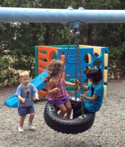 kids playing on tire swing
